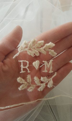 Marije heeft voor haar huwelijk met Rik hun initialen geborduurd op haar sluier